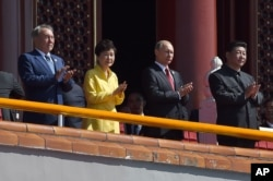 FILE - Chinese President Xi Jinping, right, applauds with, from left, Kazakhstan President Nursultan Nazarbayev, South Korea President Park Geun-hye and Russia's President Vladimir Putin, during a parade to mark the 70th anniversary of Japan's surrender.