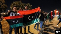 Des Libyens brandissent le drapeau national lors de la célébration du septième anniversaire de la chute de Moammar Kadhafi, à Benghazi, dans l'est du pays, le 17 février 2017