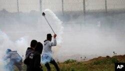 یکی از معترضان فلسطینی در حال پرتاب یک کپسول گاز اشک آور به آن طرف حصارهای مرزی بین غزه و اسرائیل - ۱۰ فروردین ۱۳۹۸