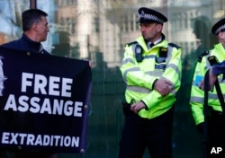 A protester looks across at police officers outside Westminster magistrates court where WikiLeaks founder Julian Assange was appearing in London, April 11, 2019.