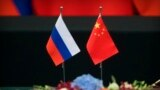 FILE - A Russian, left, and a Chinese flag sit on a table before a signing ceremony at the Great Hall of the People in Beijing, June 8, 2018.