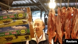 An official from the Taipei City Department of Health inspects a beef stall in a traditional market with reporters in Taipei, March 22, 2012.