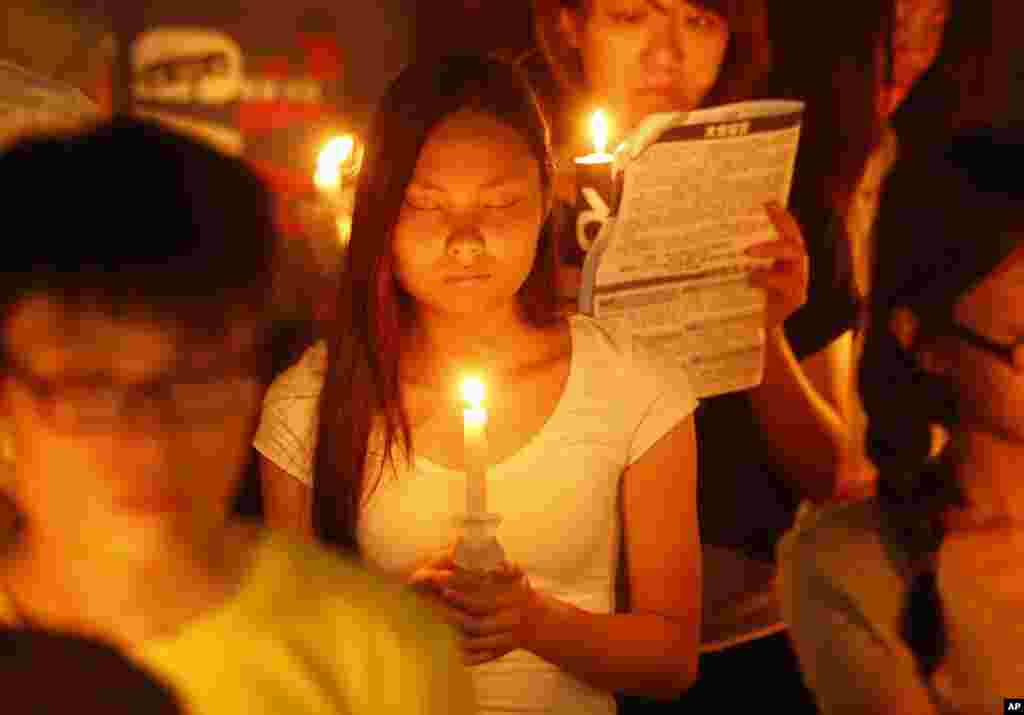A woman closes her eyes as she joins tens of thousands of people attending a candlelight vigil at Victoria Park in Hong Kong to mark the 25th anniversary of crackdown in Tiananmen Square, June 4, 2014.