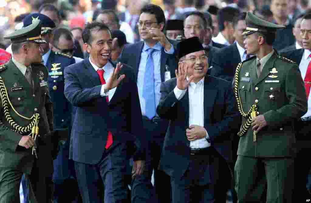 Indonesia's President Joko Widodo walks with his Vice President Jusuf Kalla in Jakarta, Indonesia, Oct. 20, 2014.