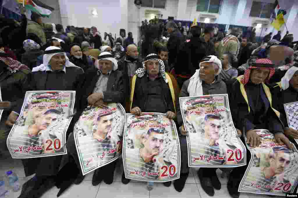 Palestinians hold posters depicting Palestinian prisoner Naim Shawamreh as they wait for the released prisoners to arrive in Ramallah, West Bank, Dec. 30, 2013.