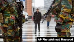 Belgian soldiers patrol the EU headquarters in Brussels on Monday, Jan. 19, 2015. Security has been stepped up after thirteen people were detained in Belgium in an anti-terror sweep following a firefight in Verviers. Two suspected terrorists were killed. (AP Photo/Virginia Mayo)