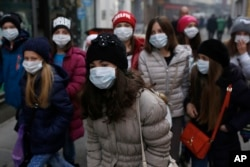 A group of school children walk on street with face mask in Sarajevo, Bosnia, on Wednesday, Dec. 23, 2015.