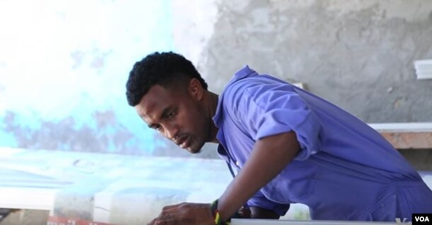 Shafii Ali returned home to Somalia after living in a refugee camp in Kenya. He is now learning to make window frames.