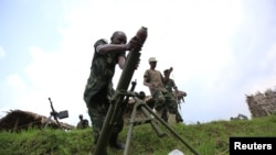 M23 rebel fighter loads an 82mm mortar bomb at their defense position in Karambi, eastern Democratic Republic of Congo (DRC) in north Kivu province, near the border with Uganda, July 12, 2012.