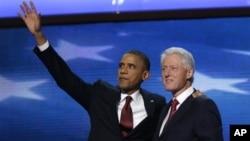 Başkan Barack Obama, kendisine destek konuşması yapan eski Başkan Bill Clinton'la birlikte izleyicileri selamlarken