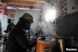 "FILE - A woman makes coffee in a kitchen in the Oceti Sakowin camp as ""water protectors"" continue to demonstrate against plans to pass the Dakota Access pipeline near the Standing Rock Sioux Reservation, near Cannon Ball, N.D., Dec. 6, 2016."