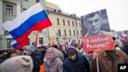 26일 러시아 모스크바 시민들이 지난 2015년 암살된 야권 지도자 보리스 넴초프의 초상과 국기를 든 채 행진하고 있다.