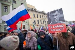 FILE - People march in memory of opposition leader Boris Nemtsov, portrait at right, in Moscow, Russia, Feb. 26, 2017. Thousands of Russians take to the streets of downtown Moscow to mark two years since Nemtsov was gunned down outside the Kremlin.
