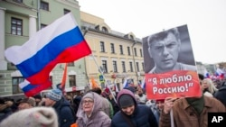 People march in memory of opposition leader Boris Nemtsov, portrait at right, in Moscow, Russia, Sunday, Feb. 26, 2017. Thousands of Russians take to the streets of downtown Moscow to mark two years since Nemtsov was gunned down outside the Kremlin. The poster reads: I love Russia.