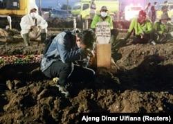 Putra Mardiansyah, 26, saat pemakaman ayahnya, Mustagor 59 tahun yang meninggal karena COVID-19, di area pemakaman yang disediakan pemerintah untuk para korban pandemi COVID-19 saat kasus melonjak, di Jakarta, 12 Juli 2021. (Foto: REUTERS/Ajeng Dinar Ulfi