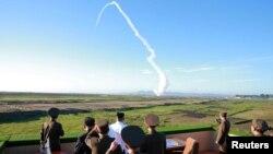 북한 김정은 국무위원장이 국방과학원에서 개발한 신형 반항공(지대공) 요격유도무기체계 시험사격을 참관했다고 조선중앙통신이 28일 보도했다. 사진은 지대공 요격미사일 발사 장면을 지켜보는 김정은(흰 상의)의 모습.