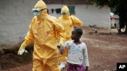FILE - Nowa Paye, 9, is taken to an ambulance after showing signs of the Ebola infection in the village of Freeman Reserve, about 30 miles north of Monrovia, Liberia, Sept. 30, 2014.