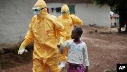 Petugas kesehatan membawa seorang anak perempuan yang menunjukkan gejala ebola di desa Freeman Reserve, Liberia (foto: dok).