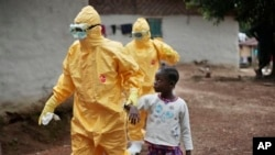 FILE - Nine-year-old Nowa Paye is taken to an ambulance after showing signs of the Ebola infection in the village of Freeman Reserve, about 30 miles north of Monrovia, Liberia, Sept. 30, 2014.