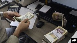 A currency exchange bureau worker counts US dollars, as Iranian bank notes are seen at right with portrait of late revolutionary founder Ayatollah Khomeini, in downtown Tehran, Iran. (file)