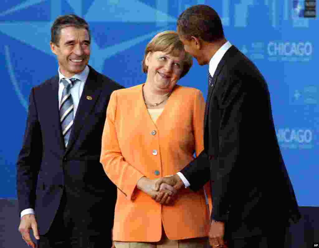 German Chancellor Angela Merkel talks to President Barack Obama as she arrives in Chicago, Sunday, May 20, 2012. At left is NATO Secretary General Anders Fogh Rasmussen. (AP)