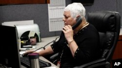 "Joyce Endresen wears an Optune therapy device for brain cancer, as she speaks on a phone at work in Aurora, Illinois, March 29, 2017. She was diagnosed in December 2014 with Glioblastoma. After two surgeries to remove the tumor as well as radiation and chemotherapy Endresen is now trying the new ""sci-fi"" cap therapy."