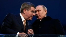 International Olympic Committee President Thomas Bach of Germany talks to Russian President Vladimir Putin during the opening ceremony of the 2014 Sochi Winter Olympics, Feb. 7, 2014.
