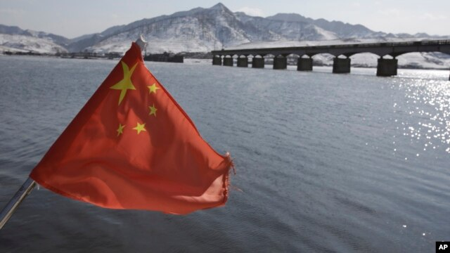 A Chinese flag is hoisted near the Hekou Bridge, right, linking China and North Korea, which was bombed in the 1950's during the Korean War, in Hekou, China, February 7, 2013.
