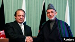 President Afghanistan Hamid Karzai (kanan) berjabat tangan dengan PM Pakistan Nawaz Sharif seusai konferensi pers bersama di Kabul (30/11).