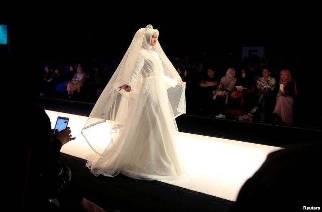 Seorang model memeragakan karya siswa, Lia Rahmawati, pada hari pertama Indonesia Muslim Fashion Festival di Jakarta, 19 April 2018.