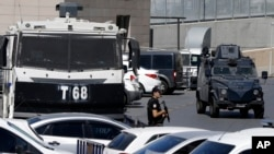 FILE - A police officer stands guard as an armored vehicle patrols outside a court building in Istanbul, Aug. 15, 2016. Authorities in the city of Konya on Thursday ordered the detention of 73 air force pilots alleged to have been part of a failed July coup.