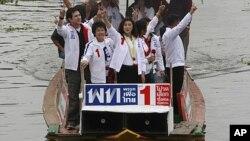 អ្នកស្រី Yingluck Shinawatra (កណ្តាល) កំពុងបក់ដៃពីកាណូតមួយក្នុងអំឡុងយុទ្ធនាការឃោសនាបោះឆ្នោតនៅតាមព្រែកមួយឯជាងក្រុងបាងកកប្រទេសថៃកាលពីថ្ងៃព្រហស្បតិ៍ទី៣០ខែមិថុនាឆ្នាំ២០១១។ អ្នកស្រីជាបេក្ខនារីនាយករដ្ឋមន្ត្រីរបស់គណបក្សប្