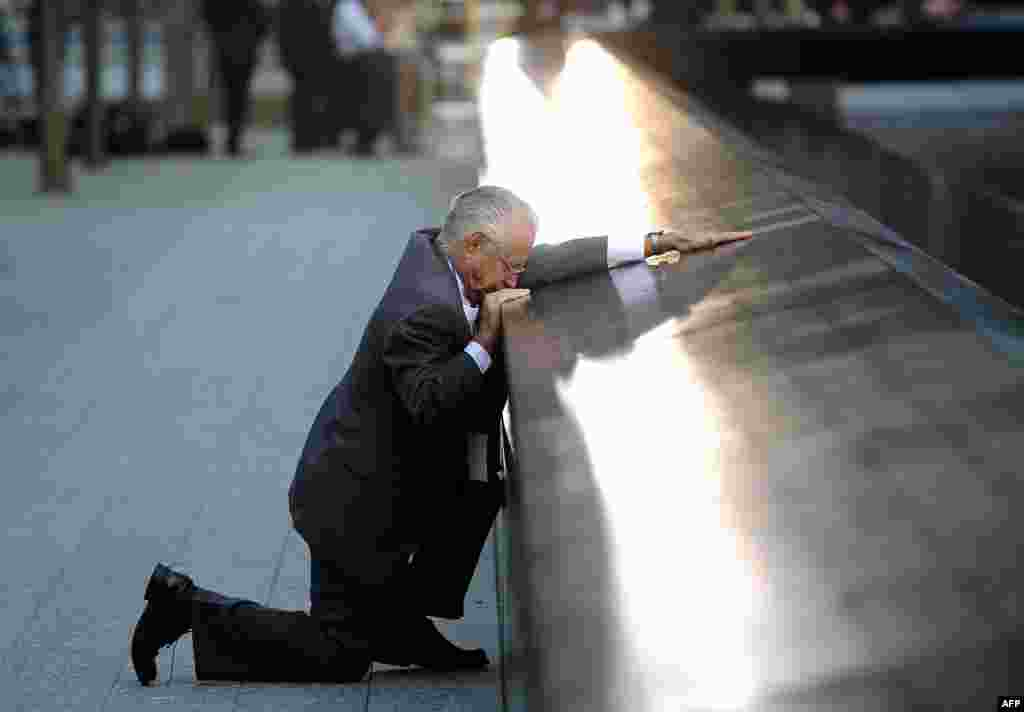 Robert Peraza pauses at his son's name at the North Pool of the 9/11 Memorial during tenth anniversary ceremonies at the site of the World Trade Center in New York, September 11, 2011. (Reuters)