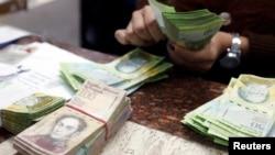 FILE - A cashier counts bolivars at a money exchange in Caracas, Venezuela, Feb. 24, 2015.
