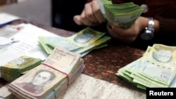FILE - A cashier counts bolivars at a money exchange in Caracas, Venezuela, Feb. 24, 2015.