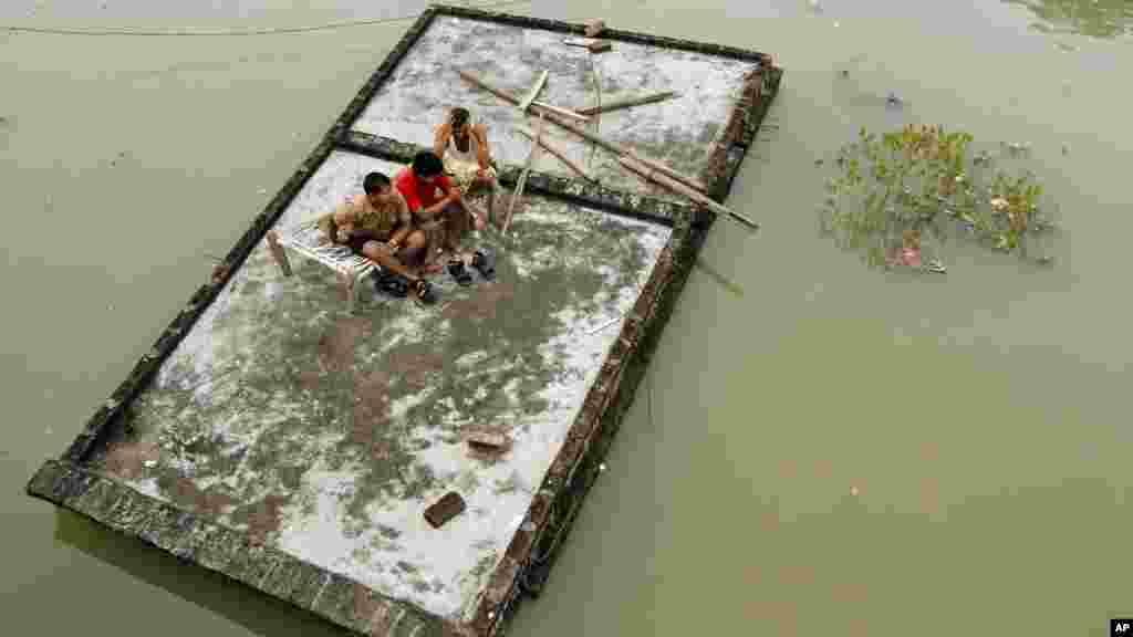 Indijci na krovu kuće, poplavljene nakon obilnih monsunskih kuša nadošlim vodama rijeke Gang.