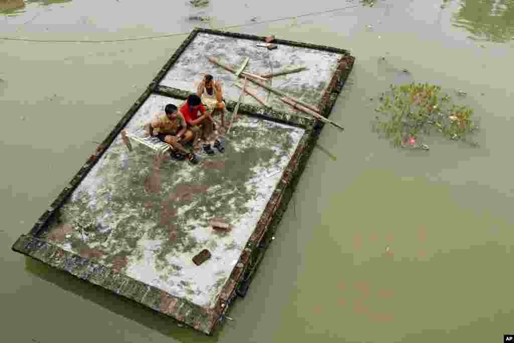 Indian men sit on the roof of a house which is submerged in the floodwaters of the River Ganges after heavy monsoon rains in Salori, India.