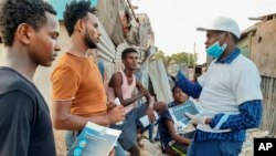 In this photo taken Wednesday, May 20, 2020, stranded Ethiopian migrants receive informational materials informing them how to protect themselves against the coronavirus, in Bosaso, Somalia. (International Organization for Migration (IOM) - Somalia via AP)