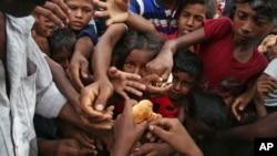 ເດັກນ້ອຍອົບພະຍົບໂຣຮິງຢາ ທີ່ຫລົບໜີຈາກມຽນມາ ໄປຢູ່ບັງກລາແດັສ ຢື້ມືໄປຮັບເອົາອາຫານ ທີ່ແຈກຢາຍໃຫ້ ໂດຍ ຄົນໃນທ້ອງຖິ່ນ ຢູ່ Kutupalong ທີ່ໃຊ້ເປັນສູນອົບພະຍົບຊົ່ວຄາວ ຢູ່ເຂດ Bazar ຂອງເມືອງ Cox ໃນບັງກລາແດັສ ໃນວັນທີ 30 ສິງຫາ, 2017.