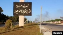 """A sign which reads in Arabic, """"The city of Sirte, under the shadow of Sharia"""" is seen as smoke rises in the background while forces aligned with Libya's new unity government advance on the eastern and southern outskirts of the Islamic State stronghold of"""