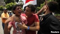 8일 이집트 군부가 무르시 대통령을 지지하는 무슬림형제단 시위대에 발포한 가운데, 총격으로 동료를 잃은 시위대 일원이 오열하고 있다.