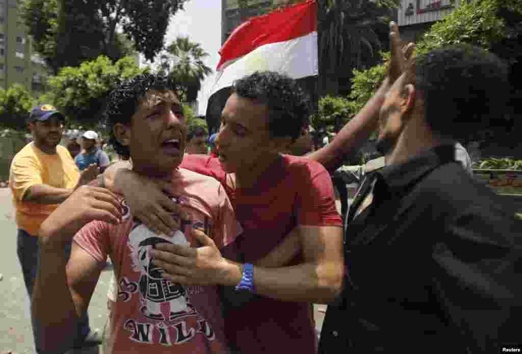 8일 이집트 군부와 무르시 대통령을 지지하는 무슬림형제단이 유혈 충돌한 가운데, 군부의 총격으로 동료를 잃은 시위대 일원이 울고 있다.
