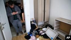 Polisi berpakaian preman di dalam apartemen tempat tinggal tersangka pembantaian kelab malam dalam razia di Istanbul (17/1). (AP/Lefteris Pitarakis)