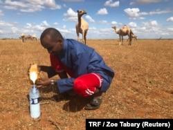 A client of Gedi Mohammed fills a water bottle with fresh camel milk in Hadado, Kenya, June 30, 2018.