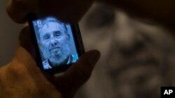 Un hombre toma una foto a un retrato de Fidel Castro en el monumento a José Martí en La Habana.