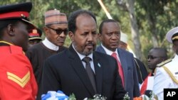 Somalia's President Hassan Sheikh Mohamud, center, lays a wreath as Kenya's President Uhuru Kenyatta, center right, and President Muhammadu Buhari of Nigeria, center left, stand behind at an interfaith memorial service honoring Kenyan soldiers killed whil