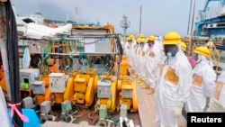 Members of a Fukushima prefecture panel, which monitors the safe decommissioning of the nuclear plant, inspect the construction site of the shore barrier, Aug. 6, 2013.