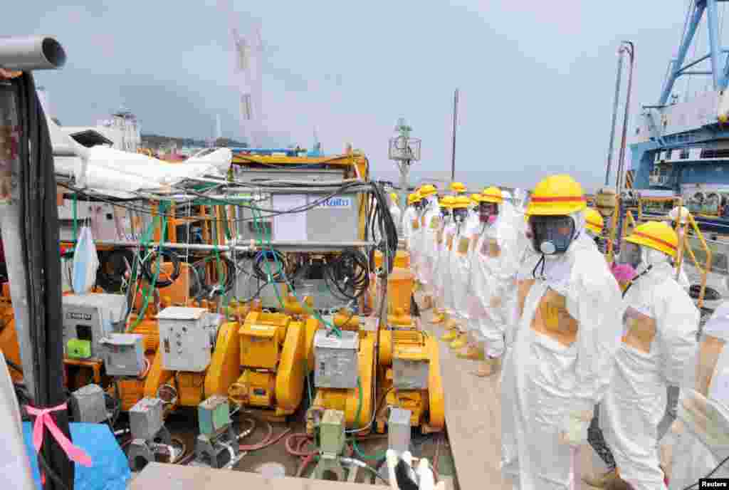 Members of a Fukushima prefecture panel, which monitors the safe decommissioning of the nuclear plant, inspect the construction site of the shore barrier, August 6, 2013.