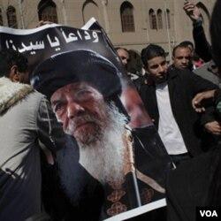 Warga Kristen Koptik Mesir membawa gambar pemimpin Gereja Koptik, Paus Shenouda, yang meninggal dunia hari Sabtu (17/3).