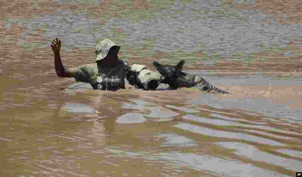 """Un exercice de simulation montrant un chein dressé appréhendant un """"braconnier de rhino"""", au centre, après la descente d'un hélicoptère dans l'eau, dans une académie dirigée par le Groupe Paramount, près de Rustenburg, Afrique du Sud, 26 novembre 2014."""